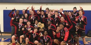 With medals around their necks and the trophy in their hands, the boys' wrestling team poses for a team picture after winning the State Dual Championship.