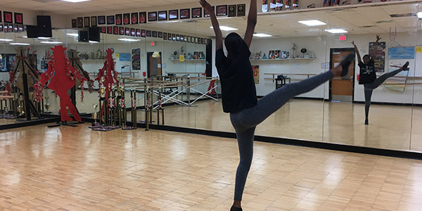 Demonstrating a fan kick, junior Chloe Baines practices her solo choreography.