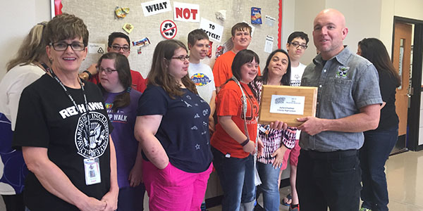 With the school's recycling team looking on, Frisco ISD District Recycling Coordinator Seth Williams (right) presents the High School Most Recycled Materials award to teacher Julia Chalker (left).