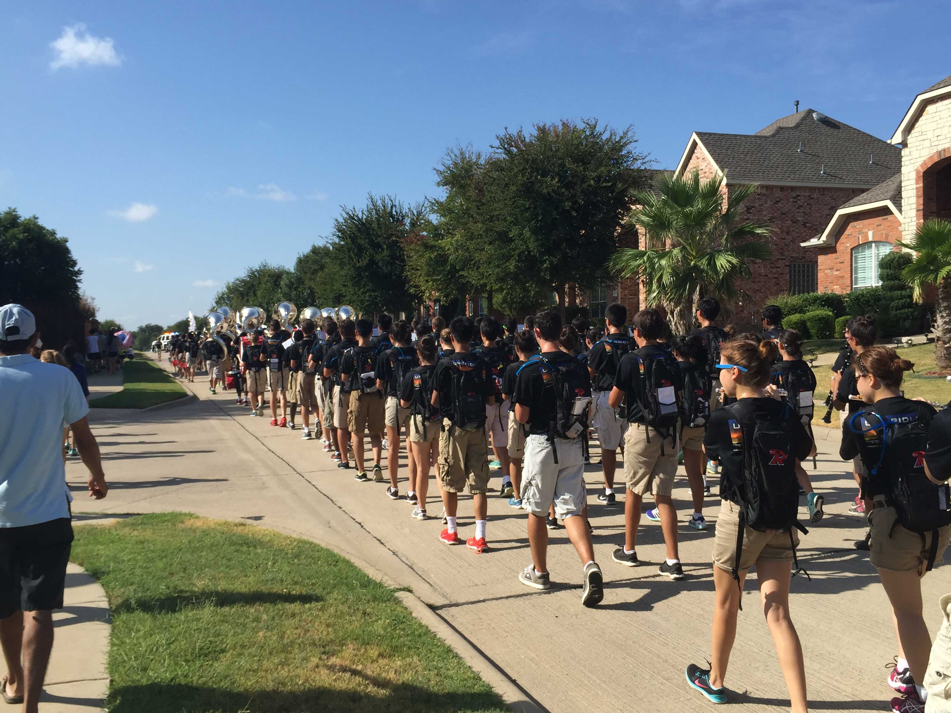 Making their way through the Turnbridge Manor and Hunters Creek neighborhoods, the school's marching band filled the street, temporarily preventing cars from driving down it.
