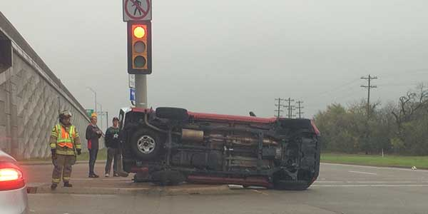 The truck of senior Gunter Hawk sits on its side against the street light at Independence and 121 after an accident flipped it over on its side.