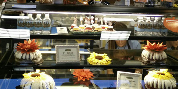 A large display case offering different sizes and flavors of bundt cakes greets customers when they walk into the store.