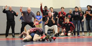 Leaning over with one hand on his thigh, head wrestling coach Jason Thurston put two fingers in the air as senior Austin Bailey scores two points for a takedown in his consolation semifinal match.