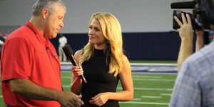 Conducting an interview on the field before the season opening game at the Ford Center at The Star, NFL Network reporter Jane Slater stands with head football coach Chris Burtch.