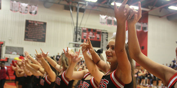 Fingers interlocked, the cheerleaders help lead the student body in the school's fight song at the senior pep rally.