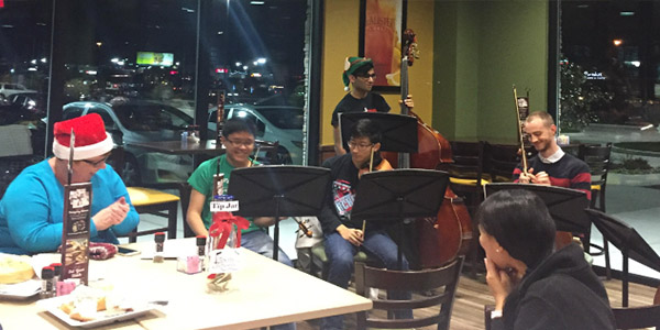 Flanked by orchestra director Julie Blackstock (far left) and assistant director Chase Fickling (back right), orchestra members Henry Cheong (violin), Maxwell Fu (violin), Nikith Kandunuri (bass) and Fowler student teacher Victoria Lien sit at McAlister's Deli as part of a orchestra in December.