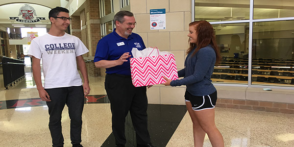 A Season of Giving fundraiser netted $1109 in student and staff donations that were presented by to Samaritan Inn Chief Executive Officer Rick Crocker by senior Jessica Gerlacher (right) and  senior Josh Rubio (left) on Friday in the rotunda.