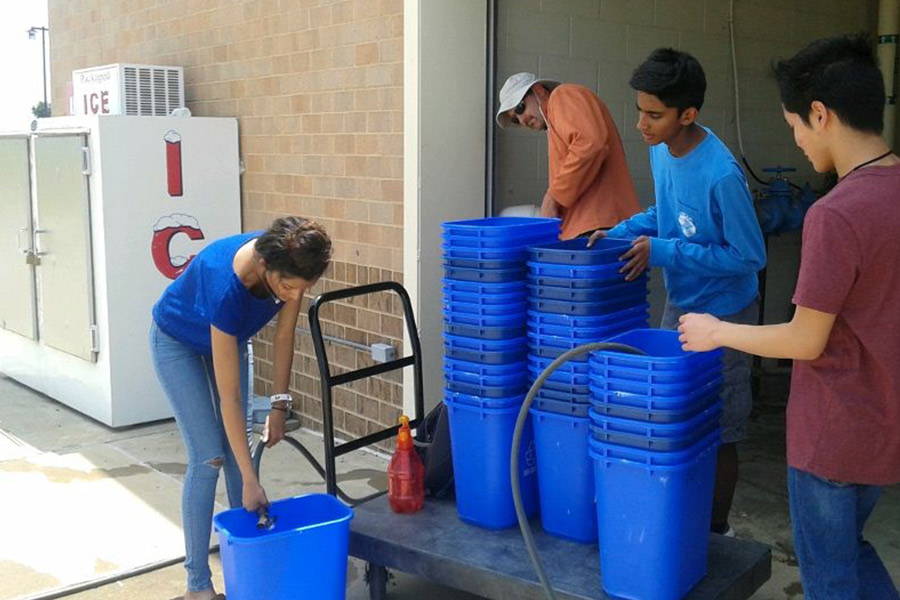 Filling+up+dozens+of+recycling+containers+with+water%2C+sophomores+Prachurjya+Shreya+%28left%29%2C+Aten+Kumar+%28center%29+and+Tay+Nguyen+%28right%29+help+JWAC+sponsor+Tim+Johannes+%28back+center%29+get+ready+for+Wednesday%27s+Pledge+to+end+Poverty+event.+
