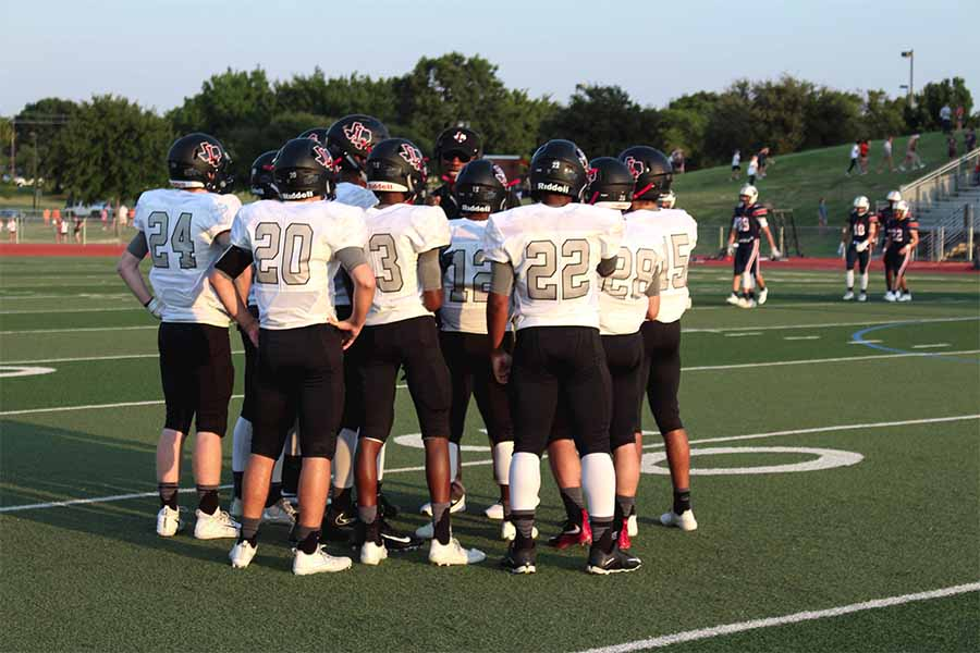 The+football+team+huddles+up+with+Coach+Burtch+prior+to+game+time.