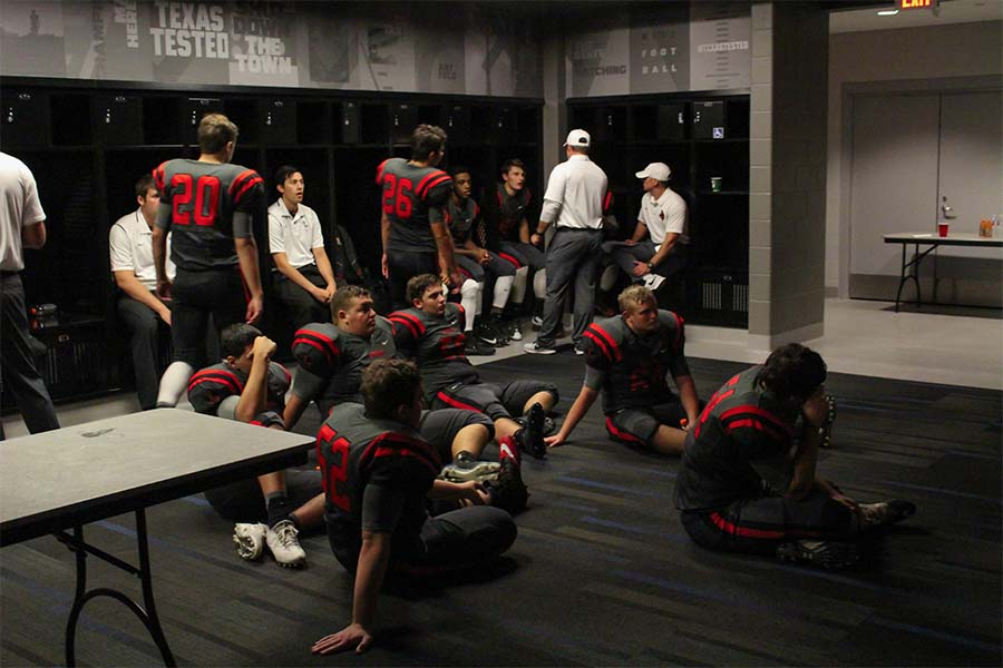 Sitting in the locker room at The Ford Center, the football team discusses strategy  on Sept. 8 game against Sherman. 0-2 after its first two games, the Redhawks go for their first win Friday against Prosper.