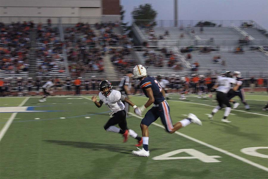 Blake+Battle+sprints+down+the+field+as+he+watches+Wakeland+to+prevent+an+interception.