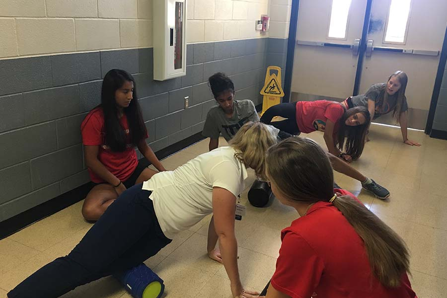 Demonstrating how to use a foam roller,  Baylor Scott and White Sports Therapy and Research athletic trainer Kathryn Niebel worked with the girls' cross country team Thursday morning.