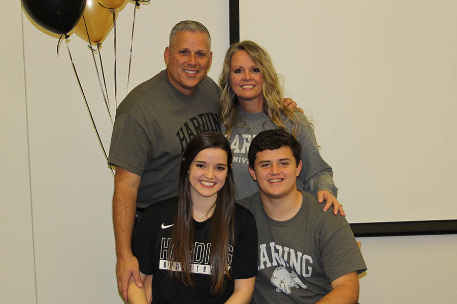 With her brother Josh by her side, and parents Chris and Christa standing behind her, senior Katelyn Burtch celebrates her signing with Harding University to continue her basketball career.