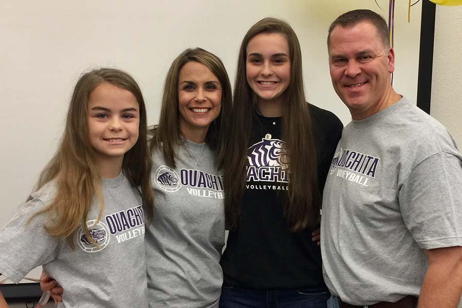 After signing with Ouachita Baptist University to continue her volleyball career, senior Madeline Hogan takes a family picture with her sister Meren, mom Delight, and dad Brian.