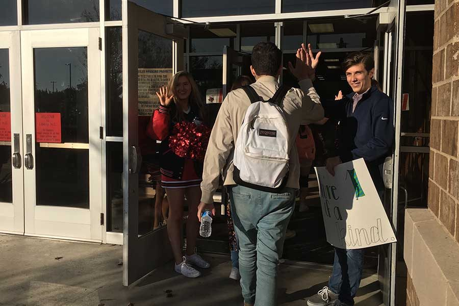 Pulse+vice+president+Wade+Glover+and+cheerleader+Peyton+Leonard+welcome+senior+Noah+Servigon+with+a+high+five+on+the+second+High+Five+Friday.+