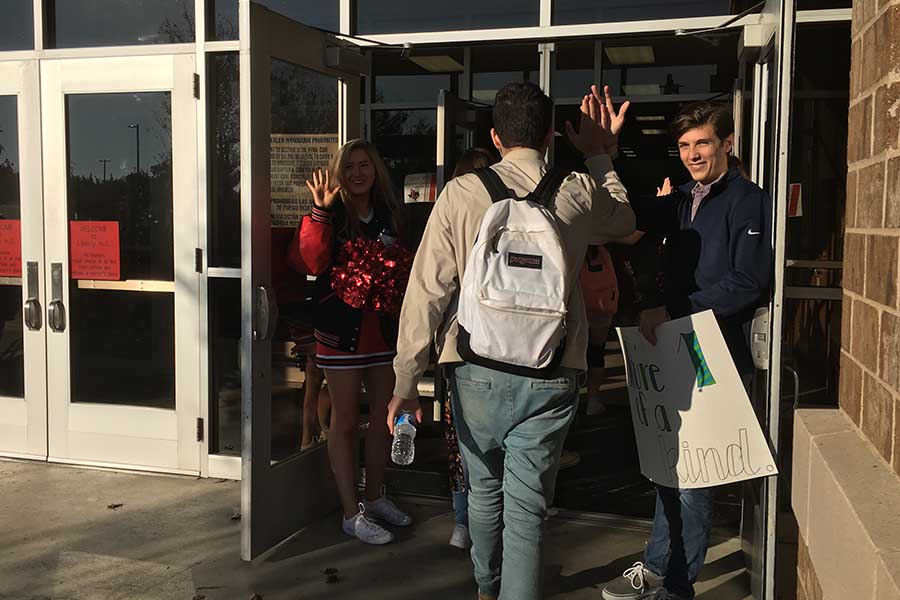 Pulse vice president Wade Glover and cheerleader Peyton Leonard welcome senior Noah Servigon with a high five on the second High Five Friday.