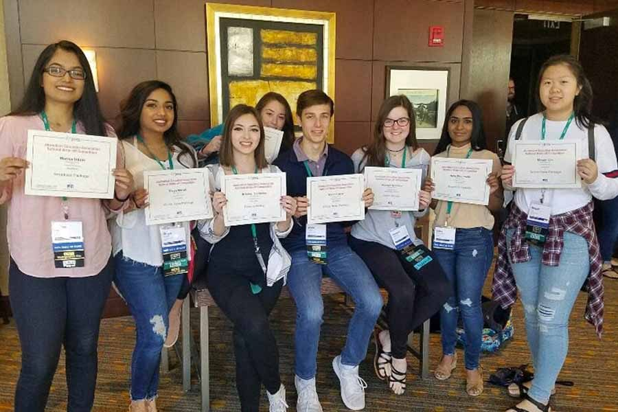 Wingspan and WTV students Marisa Uddin, Divya Murali, Brooke Colombo, Mady Daddario, Wade Glover, Keegan Williams, Neha Perumall and Megain hold up their award certificates at the end of the JEA/NSPA Fall National High School Journalism Convention in Dallas.