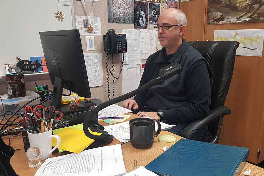 Working at his desk, social studies department head Jeff Crowe previously taught AP European History but doesn't know if the class will be offered next year.