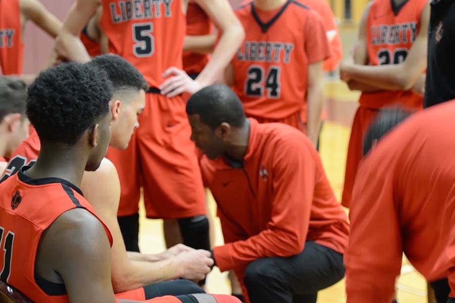 Talking to his team during a break in action, head coach Stephen Friar goes over a play.