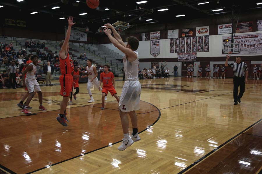 Over+the+outstretched+hands+of+a+McKinney+North+defender%2C+senior+Dylan+Shusterman+takes+a+3-point+shot+during+the+Redhawks+45-39+win+on+Tuesday%2C+Feb.+20%2C+2018+at+Plano+Senior+High+School.+