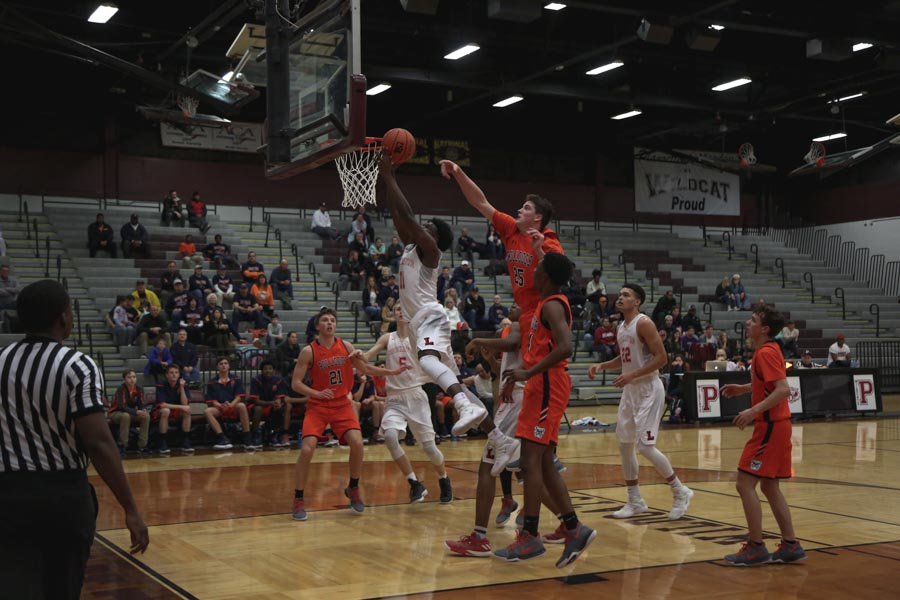 Driving+to+the+basket%2C+junior+Zion+Richardson+lays+the+ball+up+during+the+Redhawks+first+round+playoff+game+against+McKinney+North+at+Plano+Senior+High+School.+Richardson+would+finish+9+points+on+the+night+as+the+Redhawks+won+45-42+on+Tuesday%2C+Feb.+20%2C+2018.+