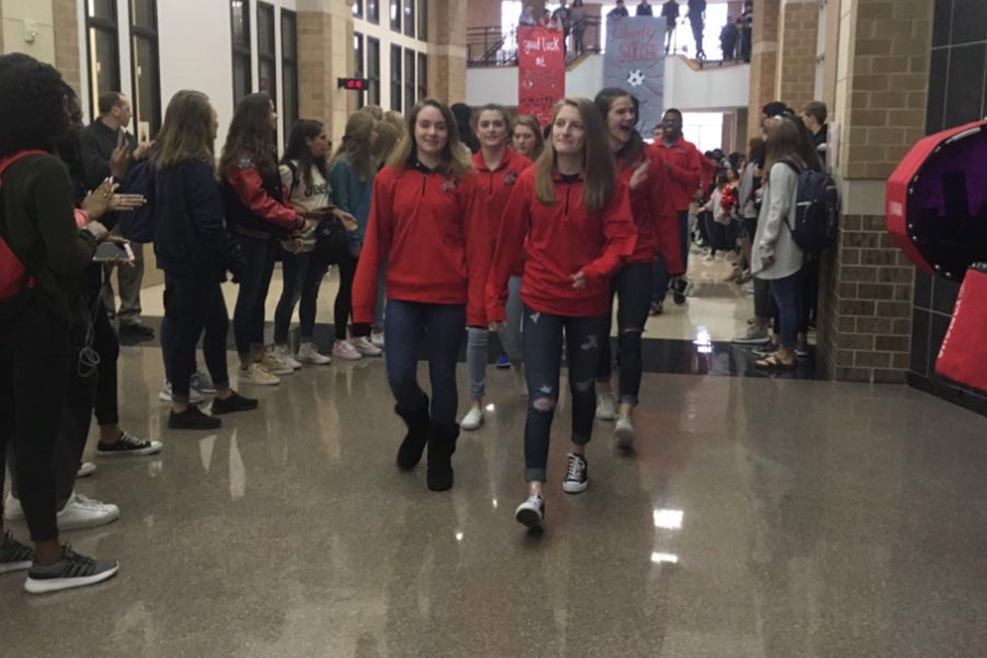 The 12 wrestlers that qualified for state make their way through the school's main hallway on Tuesday, Feb. 20, 2018 during advisory period as part of the state send-off.