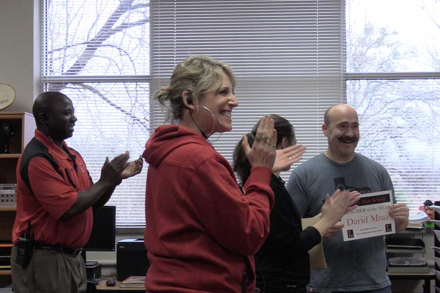 Surprised during a class, social studies teacher David Mraz received his teacher of the year certificate as assistant principals Phil Brown and Stacey Whaling, along with principal Ashley Rainwater applaud.