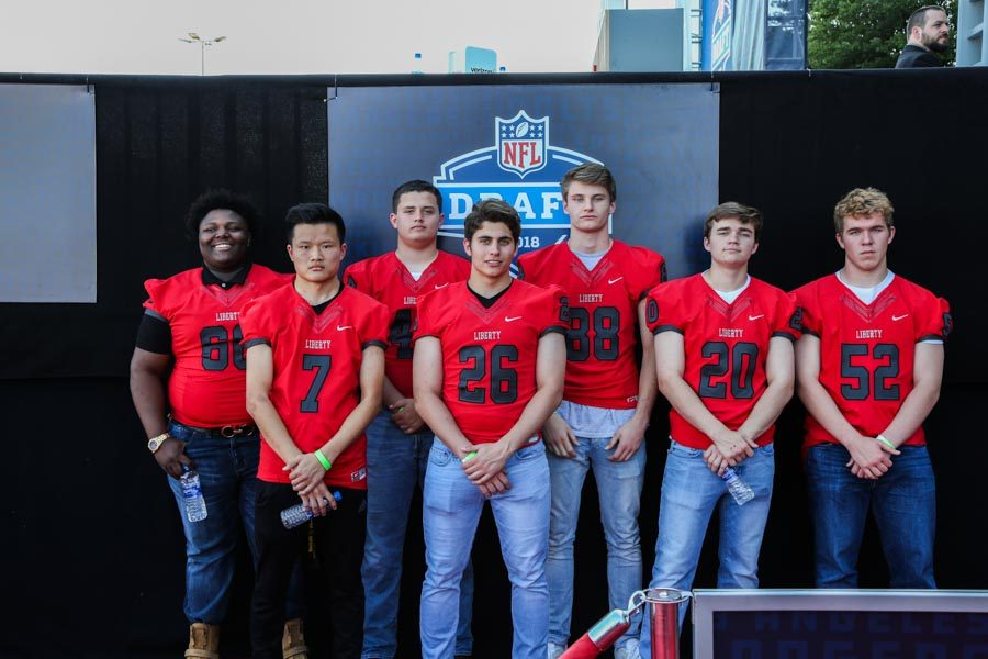 Redhawk football players stand alongside the red carpet on Friday to witness the NFL Draft.