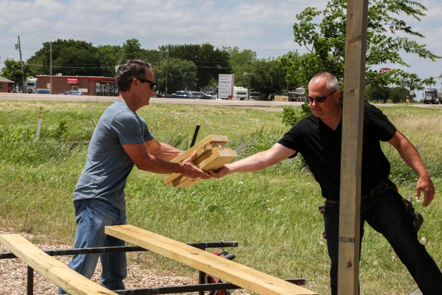 Adam Davidson hands Michael Emerson several pieces of wood to be used on the patio.