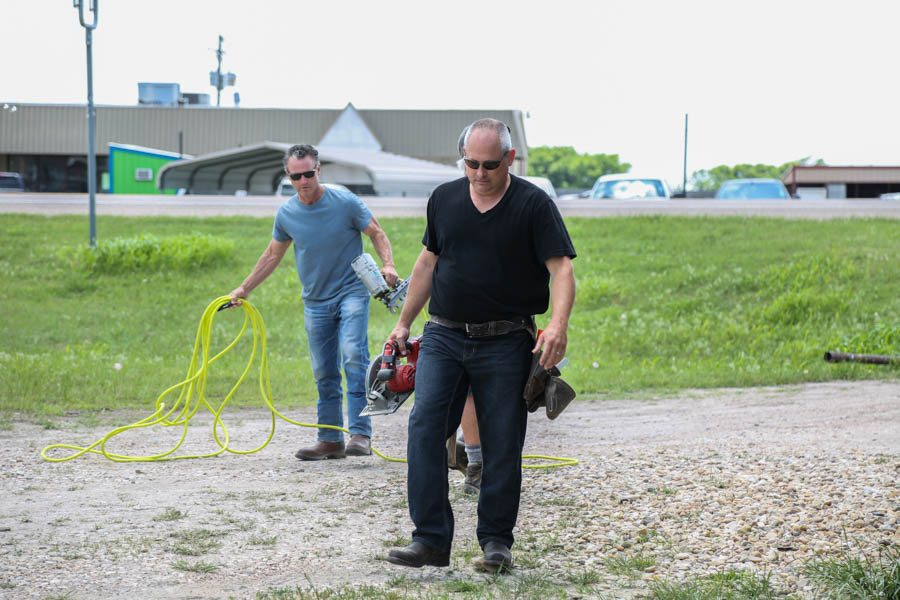 Michael Emerson and Adam Davidson prepare tools to work on the housing unit.