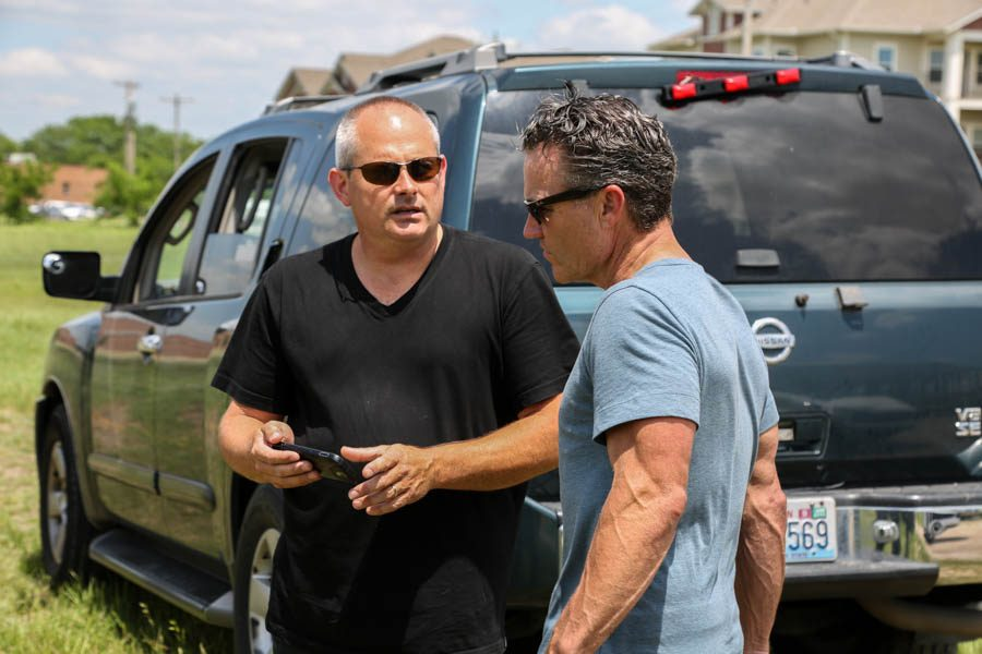Golf coach Adam Davidson speaks with his business partner Michael Emerson in Whitewright, Texas.