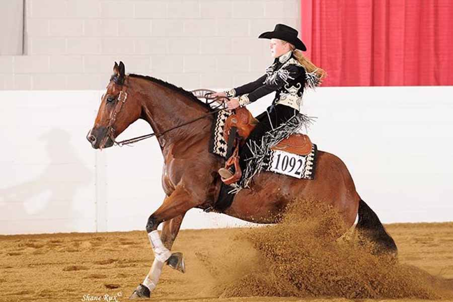 Performing a sliding stop on her quarter horse, freshman Maddie Passmore started riding at age seven and has been to the youth world more than two times since then.