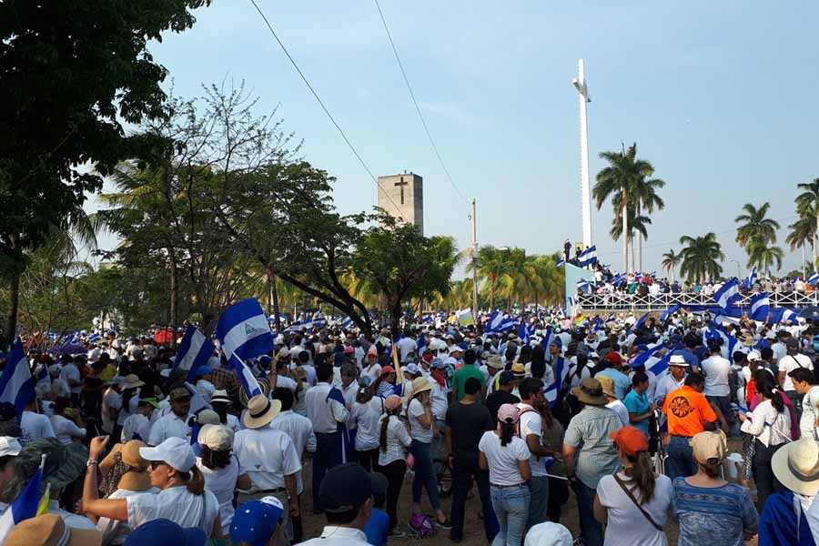 Protesters gather carrying Nicaraguan flags and dressing in the national colors, blue and white.
