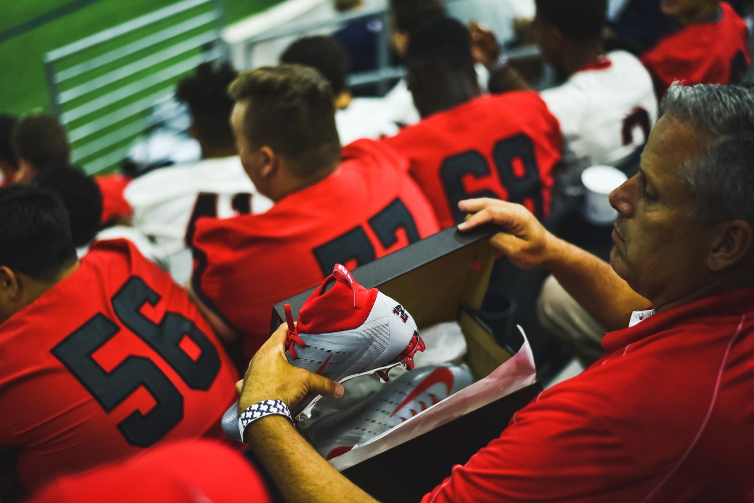 Head+football+coach+Chris+Burtch+sits+in+the+stands+at+the+Ford+Center+with+the+Liberty+Nike+custom+cleats+in+his+lap.+With+nearly+900+retweet%2C+the+Redhawks+were+at+the+Cowboys+practice+on+Tuesday%2C+August+21%2C+2018+where+they+presented+the+cleats+to+Cowboys+running+back+Ezekiel+Elliott.+
