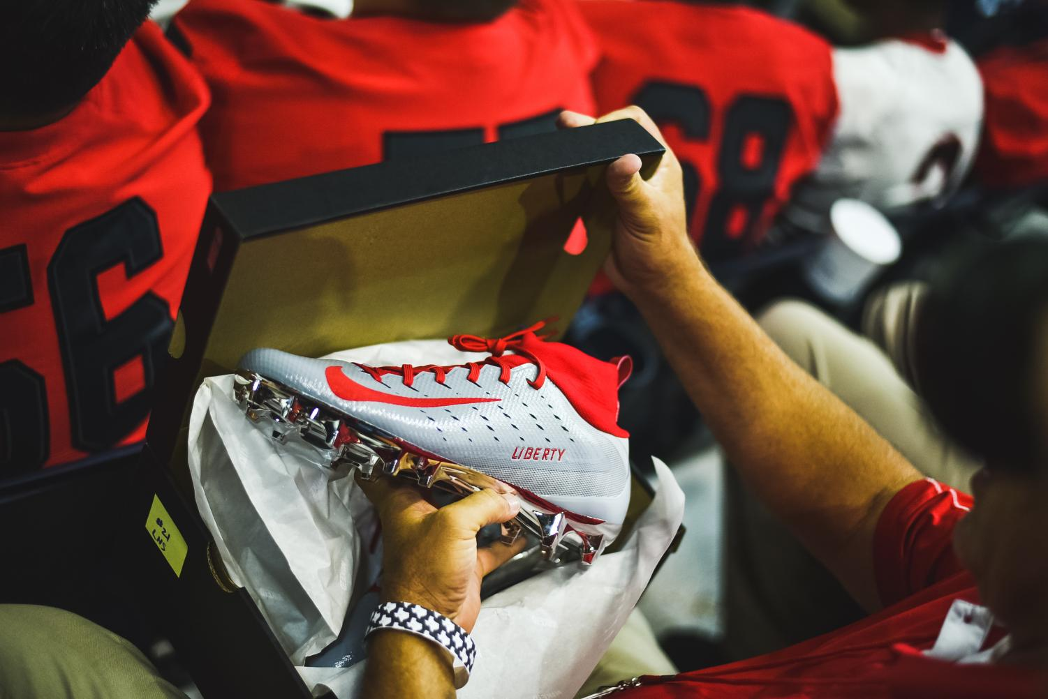 Head+football+coach+Chris+Burtch+holds+the+Liberty+custom+cleats+made+by+Nike+for+each+Frisco+ISD+school.