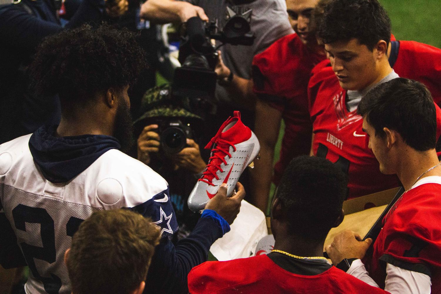 With+local+media+documenting+the+moment%2C+Cowboys%27+running+back+Ezekiel+Elliott+checks+out+the+Liberty+Redhawks+custom+cleats+made+by+Nike.+The+Redhawks+received+the+opportunity+to+present+Elliott+the+cleats+after+winning+a+social+media+contest+and+earning+the+most+retweets.