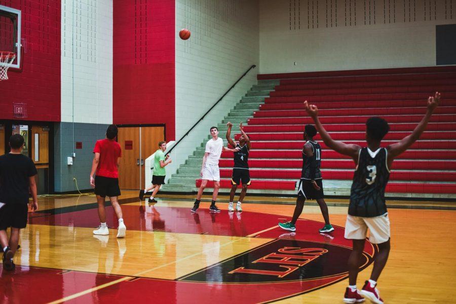 Senior+Hanard+Mabatah+shoots+a+3+pointer+while+senior+Carter+Brock+guards+him+from+outside+the+key.
