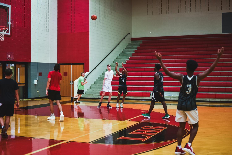 Senior Hanard Mabatah shoots a 3 pointer while senior Carter Brock guards him from outside the key.