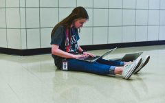 Working on a project for AP Human Geography, freshman Caitlyn Tracy sits in the hallway with her student ID dangling to her side. Enforcement of students wearing their IDs was supposed to begin Tuesday, but a delay in getting all students their IDs led to Friday being the first day for consequences.