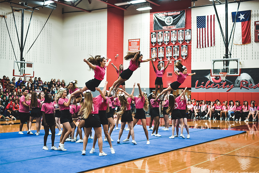 Performing one of several stunts during the Pink Out Pep Rally, cheerleaders are launched into the sky as several of their teammates wait to catch them. With the addition of a cheer class, cheerleaders would have much more time to rehearse for pep rallies and competitions as well as receiving a fine arts credit.