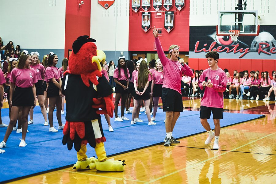 Rocky+the+Redhawk+looks+on+as+senior+Timothy+Wynia+and+senior+Fletcher+Osborne+emcee+at+the+Pink+Out+Pep+Rally+on+Friday%2C+Oct.+26%2C+2018.+Funds+raised+from+Pink+Out+shirts+support+breast+cancer+research.