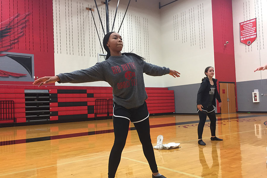 Stretching before practice, freshman Melia Terry participates in both Red Rhythm and orchestra. Having to switch off between the two, Terry will have a packed schedule performing for both in the Winter Extravaganza.