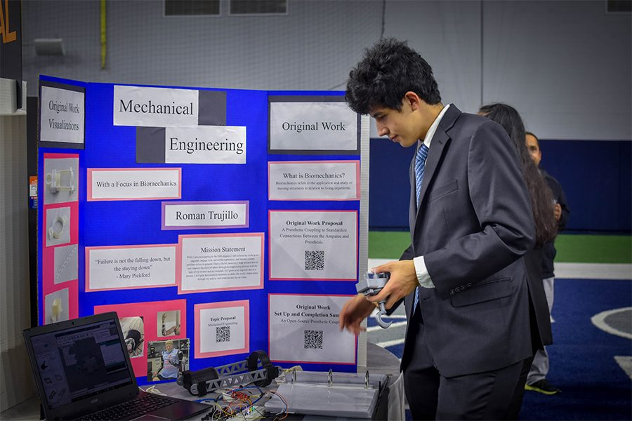 Showcasing+his+work+in+mechanical+engineering%2C+senior+Roman+Trujillo+presents+his+ideas+of+biomechanics+and+prosthetics+at+the+ISM+showcase+at+The+Star.+