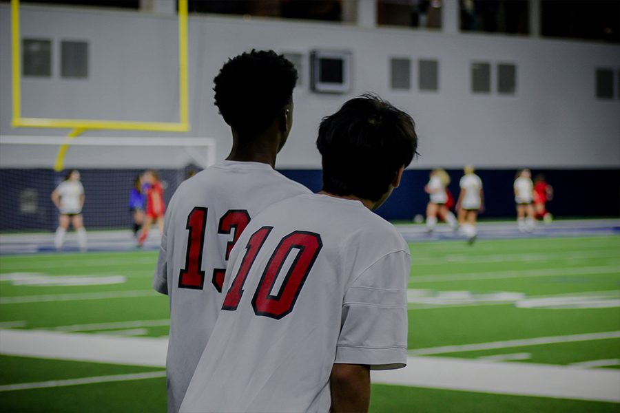 Freshman Cameron Wooley (13) and sophomore Jonathan Siv (10) watch the end of the Varsity girls soccer game at the Ford Center at The Star on Friday, January 11th.