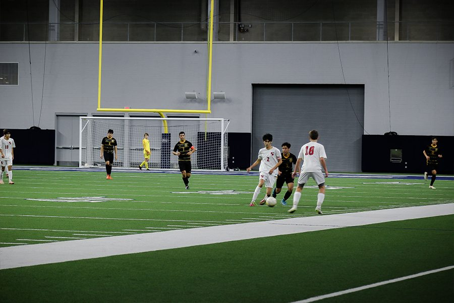 Senior and captain Nicholas Siv (2) passes the ball to sophomore Aaron Boehmer (18) in attempt to keep the ball away from the Warriors on Friday, January 11th at the Ford Center at The Star.