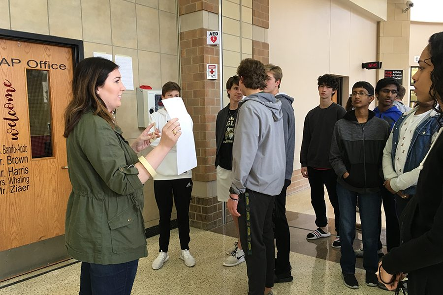 Ready to hang their  Martin Luther inspired posters listing their problems with the Student Handbook, world history students listen as teacher Kristin Mayfield tells them what to do.  The project was designed as a way to help illustrate what Martin Luther did with the Reformation.