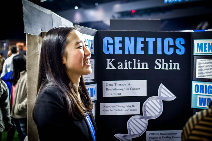 Studying gene therapy this year, senior Kaitlin Shin smiles as she discusses her original work with attendees.