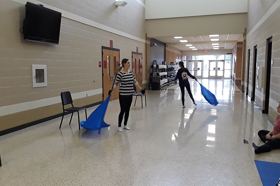Winterguard members practice spinning their flags as they prepare to travel to Coppell High School and participate in the NTCA Coppell High School Competition.