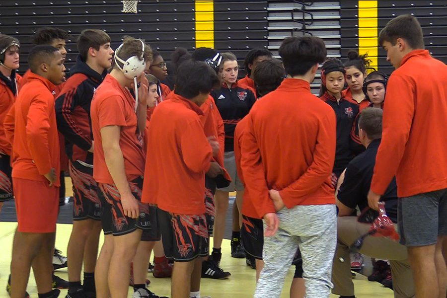 Kneeling+in+the+midst+of+a+team+huddle%2C+wrestling+head+coach+Cody+Bridwell+addresses+the+team+during+Thursday%27s+double+dual+match+against+Independence+and+The+Colony+at+The+Colony+High+School+on+Jan.+17%2C+2019.+as+both+the+boys%27+and+girls%27+teams+won+both+of+their+matches.+
