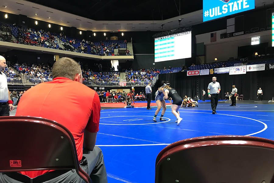 With+senior+Ashley+Cook+in+the+center+of+the+mat+during+a+state+tournament+match%2C+assistant+wrestling+coach+Justin+Koons+looks+on.+Cook+would+finish+in+2nd+place%2C+with+the+girls%27+team+also+finishing+in+2nd.+
